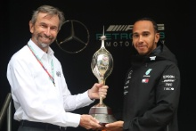 Lewis Hamilton is presented with the Hawthorn Trophy by Motorsport UK CEO Hugh Chambers